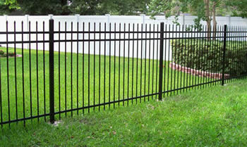 Black ornamental fence with spear top is installed on a lawn.
